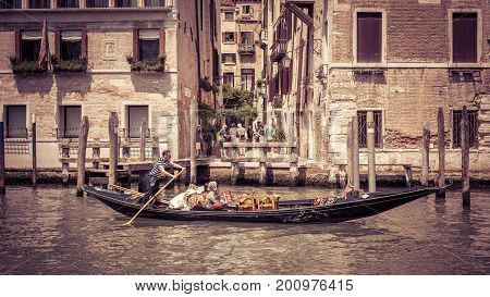 Venice, Italy - May 18, 2017: The gondola with tourists floats along the Grand Canal. Gondola is the most attractive tourist transport in Venice. 16:9 widescreen.
