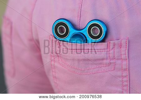 Blue Metal Popular Fidget Spinner In The Back Pocket Of Pink Jeans, Anxiety Relief Toy, Anti Stress