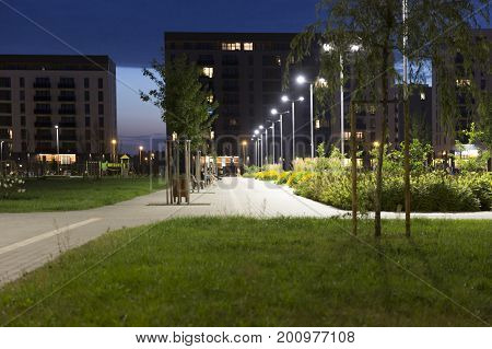 Night view of new modern residential district with park. Eco-friendly living in a city.