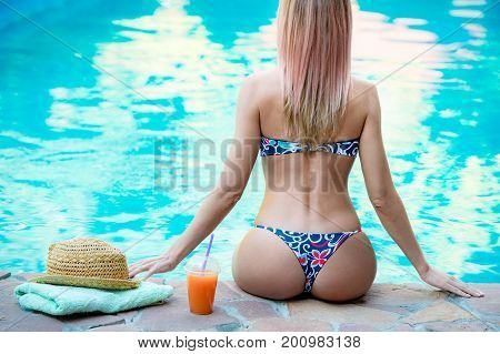 girl with perfect figure near the swimming pool enjoys her vacation