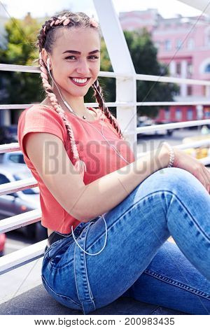 Vertical of charming youth listening to music while sitting under handrail