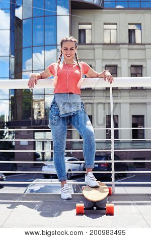 Vertical of sportive female with skateboard lining on handrail with copy space