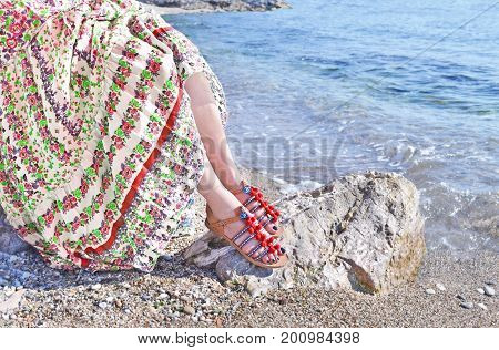 greek model advertises bohemian sandals and clothes at the beach