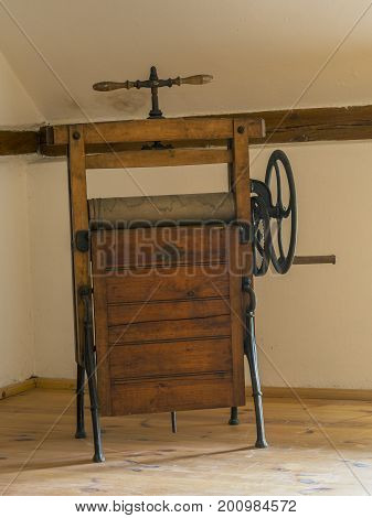 old antique wooden mangle rotary iron in attic room