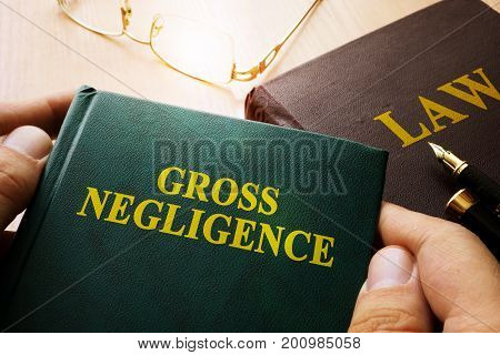 Man holding Gross Negligence book and law book.