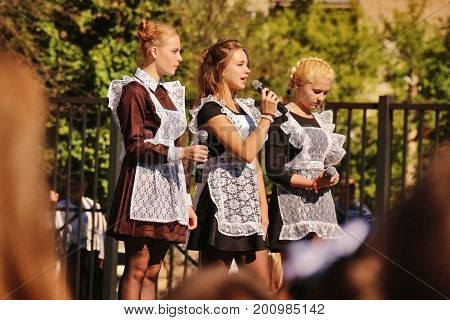 TULA RUSSIA - SEPTEMBER 1 2016: Adolescent girls in soviet school uniform with white apron say welcome speech at solemn line dedicated to Day of Knowledge in September 1