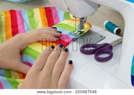 Sewing Process the sewing machine sew women's hands. sewing machine and female scissors. Woman's Hand Sewing Quilt