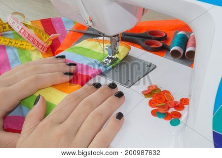 Woman hand on sewing machine.Dressmaker work on the sewing machine. Hobby sewing fabric as a small business concept. sewing machine and female scissors