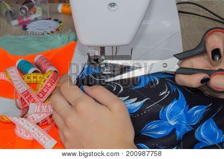 seamstress female sews clothes and put thread in needle. Workplace of tailor. people needlework and tailoring concept - tailor woman threading needle of sewing machine