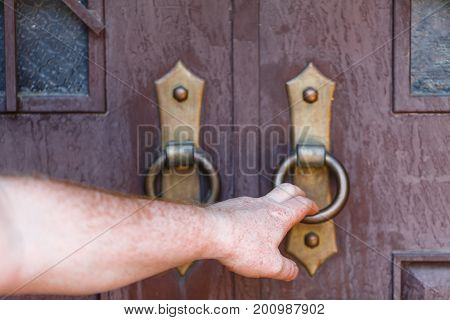 Weathered wooden door and people hand hold it