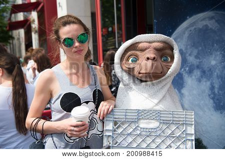 Woman Posing With Alien Figure On Sunny Summer Day