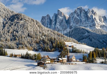 A church and some houses in the village St. Magdalena or Santa Maddalena in the Villnoesstal or Val di Funes with the Geisler Dolomites mountains in the background and fir trees on the hills under a snow cover in winter in Italy.
