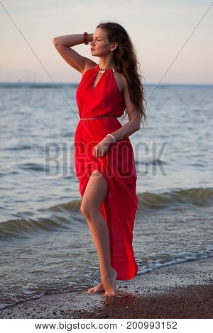 Beautiful woman in red dress standing on the sea shore