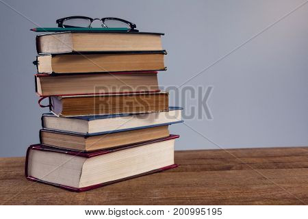 Spectacles and pencil on book stack at desk