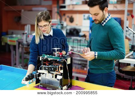 Young students of robotics preparing robot for testing in workshop