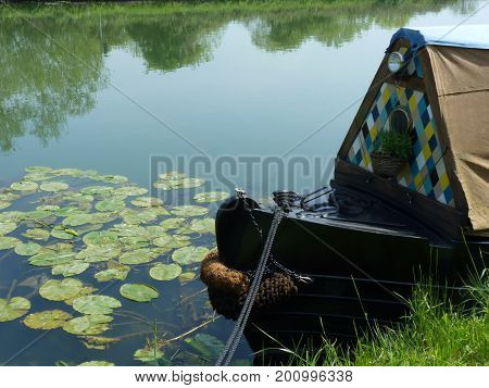 The bow of a canal barge amongst water lily pads.