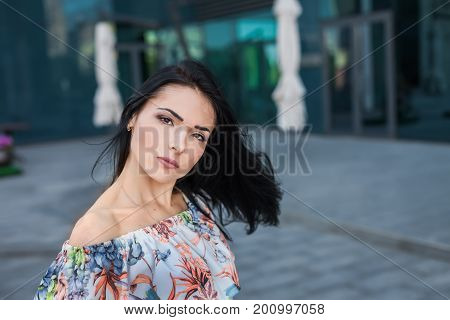 Young atractive beautiful brunette woman with long hair in the street wearing in white dress with flower pattern on the background of skyscraper