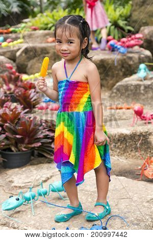 THAILAND, PATTAYA, MARCH, 10, 2015 - Little cute asian girl in a bright dress with ice cream among toy ants in Nong Nooch private botanical garden in Pattaya, Chonburi Province, Thailand