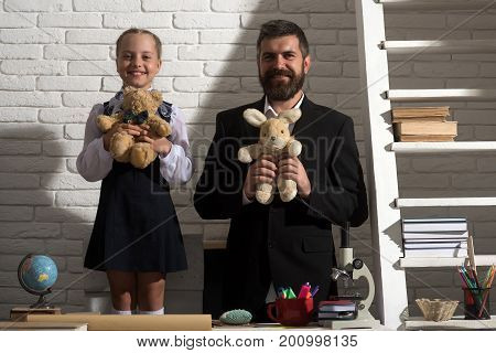 Schoolgirl And Her Dad With Smiling Faces Hold Soft Toys