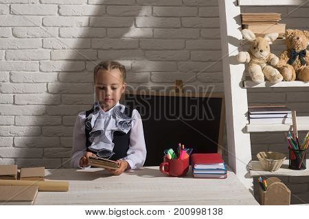 Back To School And Education Concept. Girl Sits At Desk