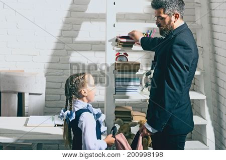 Education And Family Concept. Man And Kid Stand By Shelf