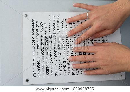 Hands of a girl reading a text written on Braille. People