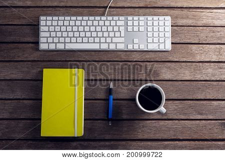 Overhead view of black coffee, pen, organizer and keyboard on wooden table
