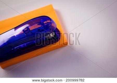 Close-up of stapler on sticky note on white background