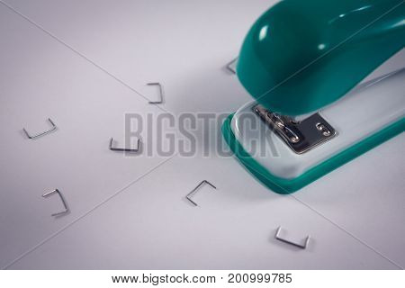 Close-up of stapler and pins on white background