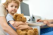 Closeup portrait of cute child sitting on mothers lap in doctors office waiting for check up hugging plush teddy bear toy poster