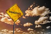 Background of dark blue sky with cumulus clouds and yellow faded road sign with text Pandemic poster