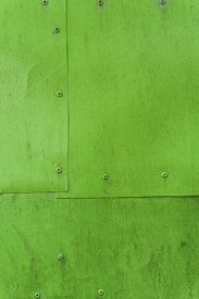 Green painted aluminium sheet background with rivets