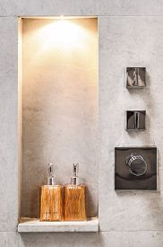 Designed bathroom with raw concrete wall decorated with bottle shelf and chrome shower valve