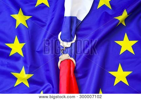 Flag Of Russia In Handcuffs On The Background Of The Flag Of The European Union. European Union Sanc
