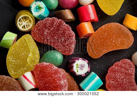 close up view of caramel multicolored candies and sugary fruit jellies on black background poster
