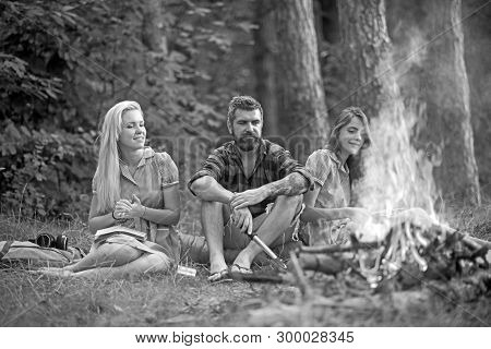 Smiling friends enjoying last summer days outdoors. Happy youngsters sitting around campfire. Girls in vintage dresses reading books while bearded man makes campfire. poster