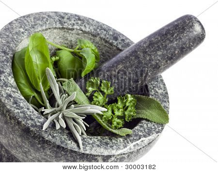 close-up of granite mortar and pestle filled with fresh herbs, isolated