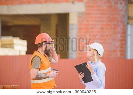 Woman Engineer And Bearded Brutal Builder Discuss Construction Progress. Construction Industry Conce