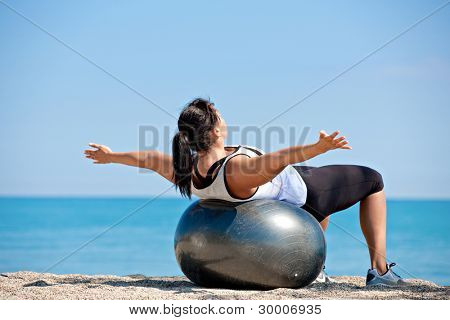 Plus Size Female Exercise Outdoor on Fitness Ball in water front