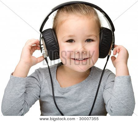 Cute little girl enjoying music using headphones, isolated over white