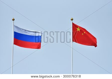 Russian And Chinese Flag, Symbol Of Friendship. China And Russia Flag Waving In The Wind Against Whi