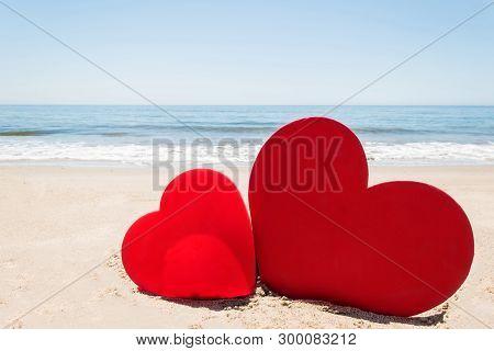 Two Hearts On The Sandy Beach Near Ocean Background.