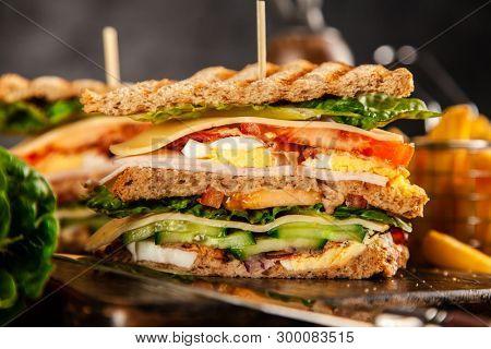 Tall club sandwich on dark background