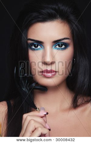 Portrait of young beautiful brunette with stylish turquoise make-up and feather in hand