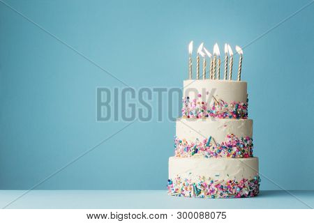 Birthday cake with three tiers and colorful sprinkles