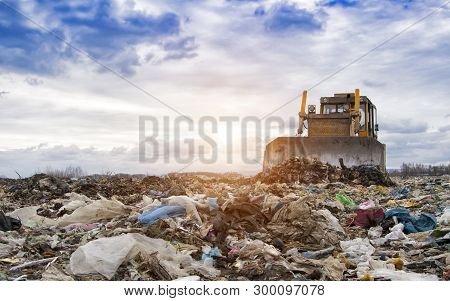 Bulldozer Working On Landfill With Birds In The Sky. Sunset
