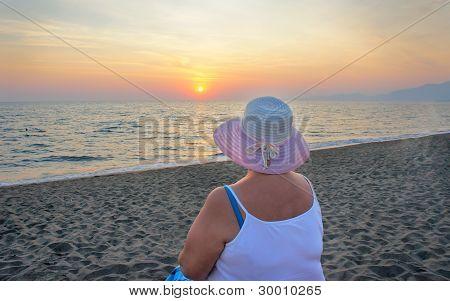 A Woman On Coastline Ocean Admires A Sunset