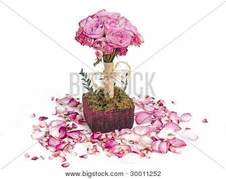 Pink roses bouquet in basket surrounded with petals