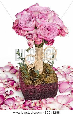 Pink roses bouquet in handmade basket surrounded with petals