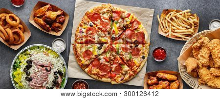 large table of assorted take out food such as pizza, french fries, onion rings, fried chicken and chicken wings